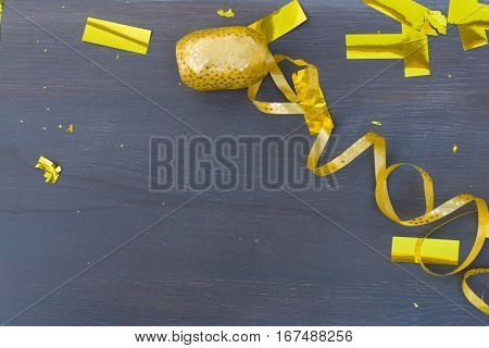 Carnaval golden confetti and streming paper decorations on dark wooden background