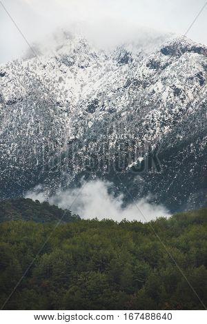 Green slopes of the Taurus mountains covered with snow and clouds in winter on gloomy day. Southern Turkey, Alanya, Dim Cay river valley
