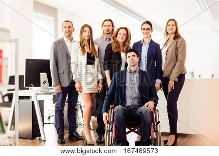 small business team posing for a group shot in their office. one man is sitting in a wheelchair.