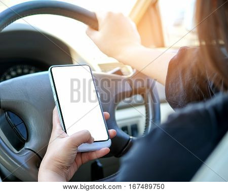 Woman using smart phone while driving a car.