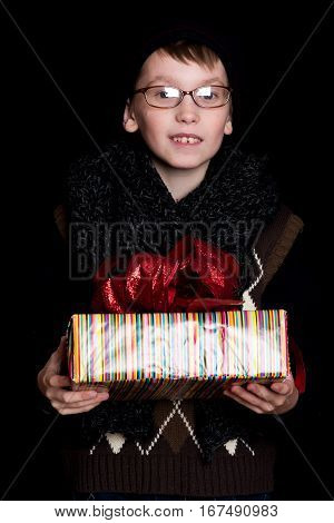 small smiling boy or cute nerd kid in glasses hat and fashionable knitted scarf on black background holds colorful present box with red bow