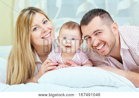 Beautiful mother, father and baby lying on the bed. Happy family, parents and a small child.