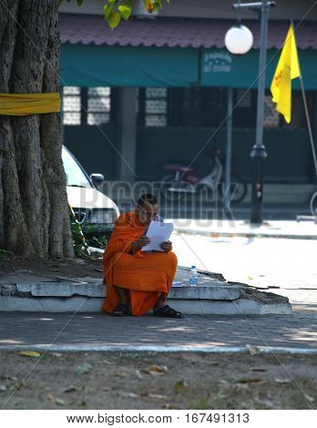 CHIANG MAI, THAILAND. February 25, 2010: Daily life in a Buddhist monastery. Buddhist monk reads a book under a tree.