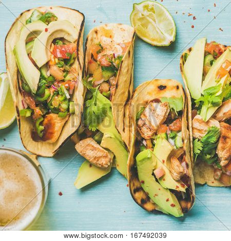 Healthy corn tortillas with grilled chicken, avocado, fresh salsa, limes and beer in glass over blue wooden background, top view, square crop. Gluten-free, allergy-friendly, weight loss concept
