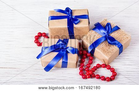 Three gift boxes made of kraft paper with blue ribbons and red coral beads. Gift boxes on a white background. Copy space