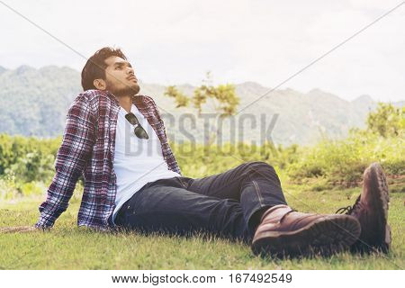 Young Man Sitting On Green Grass Thinking