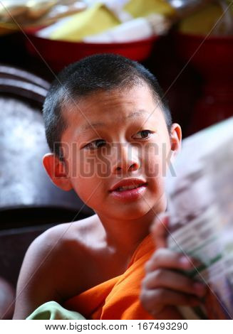 CHIANG MAI, THAILAND. February 25, 2010: Daily life in a Buddhist monastery. Closeup portrait of young boys by Buddhist monks in the monastery.