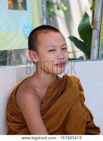 CHIANG MAI, THAILAND. February 25, 2010: Daily life in a Buddhist monastery. Closeup portrait of a little smiling boy -  Buddhist monk in a monastery.