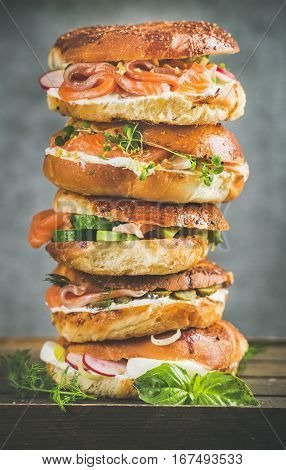 Heap of Bagels with salmon, eggs, vegetables, capers, fresh herbs and cream-cheese, grey concrete background. Healthy breakfast, lunch or take-away food concept