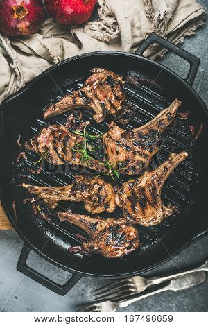 Barbecue dinner. Grilled lamb meat chops with onion and rosemary in black cast iron pan over grey background, top view. Slow food concept