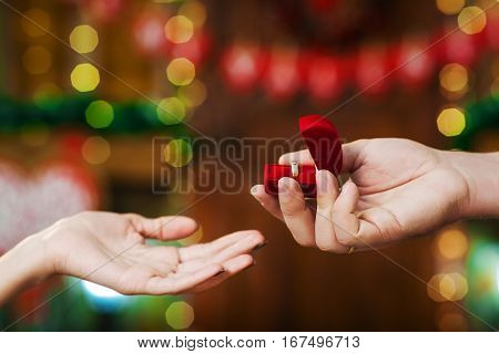Valentine's Day concept. A loving couple celebrating Valentine's Day. Lovers present each other red box with ring