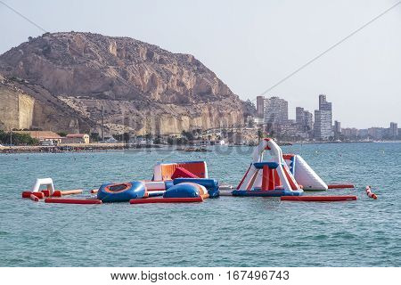 inflatable water park on the beach with the mountain and buildings of the city of alicante in the background
