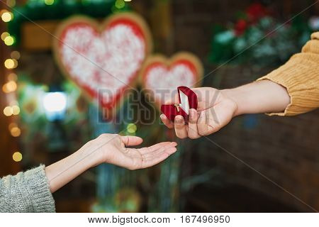 Valentine's Day concept. Teen celebrating Valentine's Day. Lovers present each other red box with ring