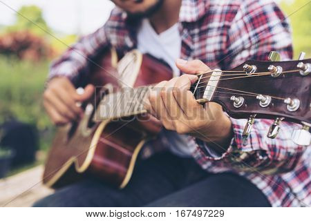 Man 's Hand Playing Guitar, Sitting On Green Grass