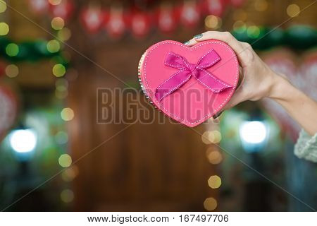Pink Box as heart with a purple bow in his hand a young girl. Valentine's Day. Women's Day. March
