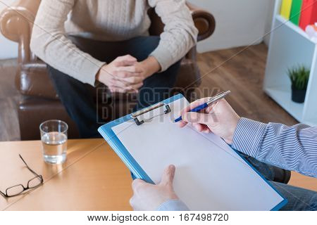 Psychologist taking notes during a psychotherapy session