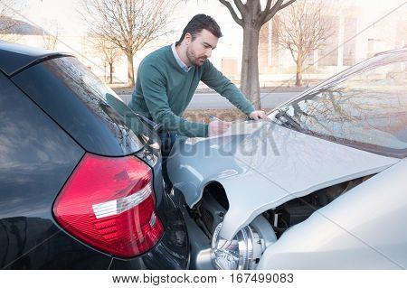 Man Writing A Car Insurance Claim After A Car Crash