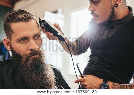 Young Man Getting Haircut At Barber Shop