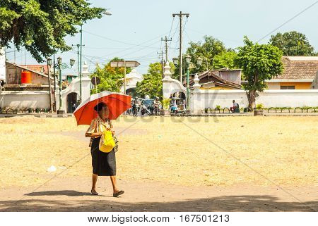 Yogyakarta, Indonesia - September 2, 2015: Old woman walking over square in the sun with umbrella next to Kraton