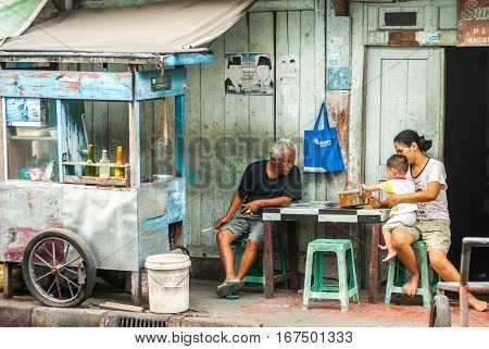 Yogyakarta, Indonesia - September 2, 2015: Scene behind the city walls with family in front of their house playing with baby waiting for customers