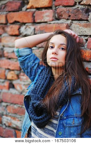 Young pretty girl with long brown hair dressed in a denim jacket a striped tee and black scarf looks pensive standing near a brick wall on the street.
