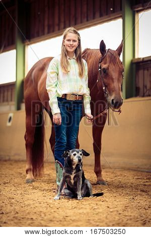 Young Cowgirl With Her Horse And Dog on horse ranch.