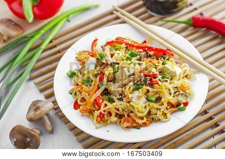 Stirred rice noodles with vegetables tofu and shiitake mushroom. Traditional Asian food.