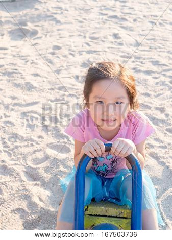 Happy Asian Child On A Seesaw In Sunset Light,sand Background