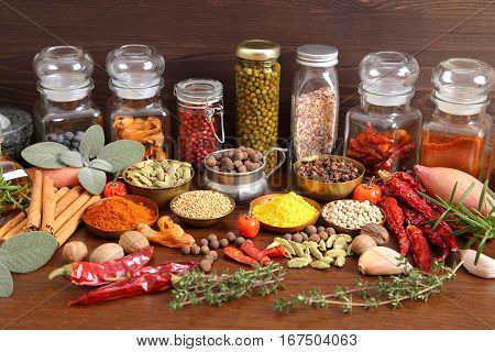 Flavorful colorful spices in metal bowls and glass bottles on dark wooden background.