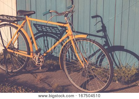 Yellow Old Vintage Bicycle Leaning Against On Vintage Wood Wall Background In The Sun. Bicycle Vinta