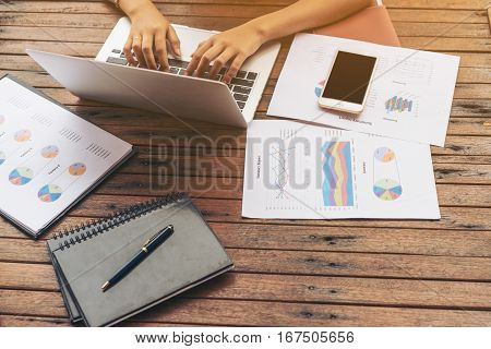 Woman's hand typing on laptop computer. Business report mobile phone and business summary laid on desk. Online and internet for business connectivity. Business work at home office. Business concept.