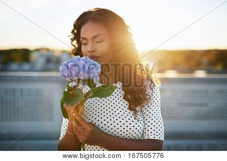 Portrait of a pretty african american woman smelling a flower