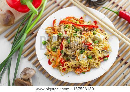 Traditional oriental food made of rice noodles vegetables shiitake and tofu. Asian meal. Top view.