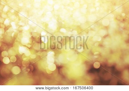 Bright glowing golden abstract bokeh background .