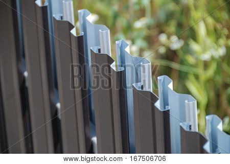 Painted sheet metal planks forming a diagonal fence line