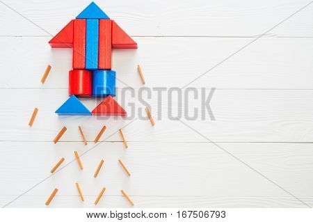 Abstract rocket from colored wooden blocks on a white wooden background with copy space. Business concept startup achievement success. Wooden puzzle in rocket shape discovery concept