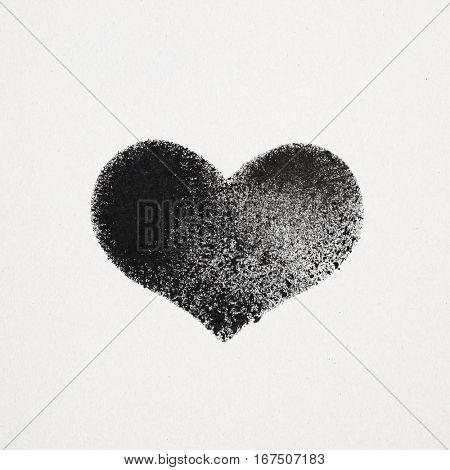 Black stenciled heart on gray cardboard