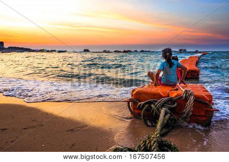 Girl and her friend in twilight at Pattaya beach and sitting on sea floating tank has a large rope bring a look to the key visual.