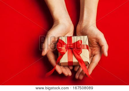 Hands holding gift in kraft box with a bow on a red background.Surprise your loved one. The concept of the day of St. Valentine's weddings engagements Mother's Day birthday New Year Christmas and other holidays. Flat fly. Place for text