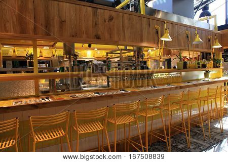 TEL AVIV, ISRAEL - APRIL 7, 2016: modern open kitchen restaurant with yellow chairs in the new Sarona food market Tel Aviv, Israel