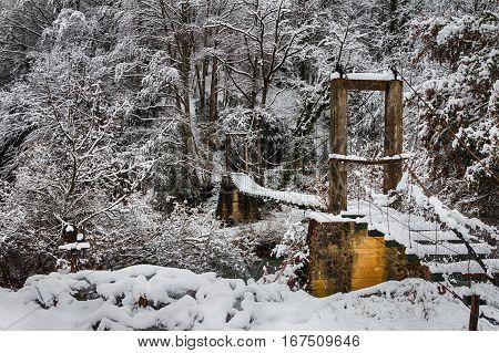 Puente colgante de madera en paisaje nevado