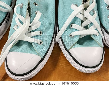 Light blue casual shoes with untied laces are on display in a store.
