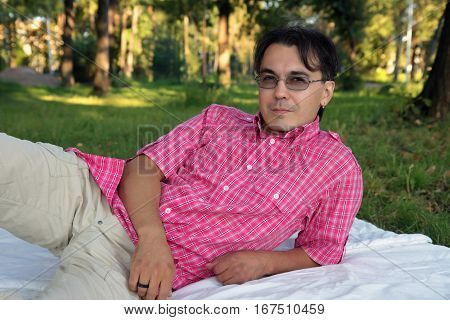 Cheerful man lying on grass at the park on beautiful sunny day