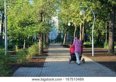 Young father with twin pram walking in summer park