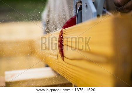 Circular saw cutting through a plank of wood