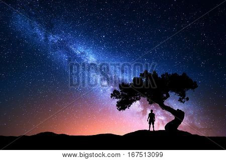 Milky Way. Night sky with stars old tree and silhouette of a standing alone man on the mountain. Milky way with red light and man on the hill. Galaxy. Silhouette of a man under the tree. Universe