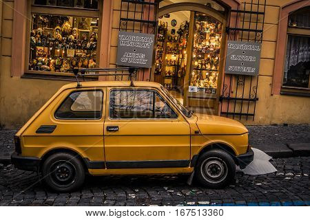 Prague Czech Republic - 3 January 2008: An old yellow Skoda parked in front of a shop selling tourist items in downtown Prague