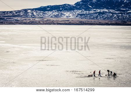 Ice fishing on a frozen reservoir in Wyoming