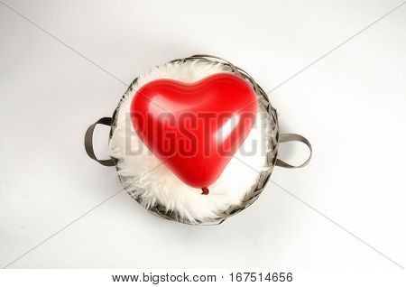 Red balloon heart in a basket with lambskin, placed center, on white background