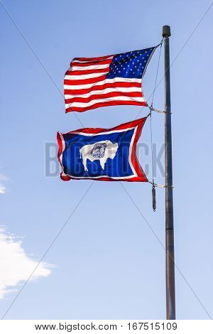 Flags of Wyoming and the United States flying on a pole with a blue sky